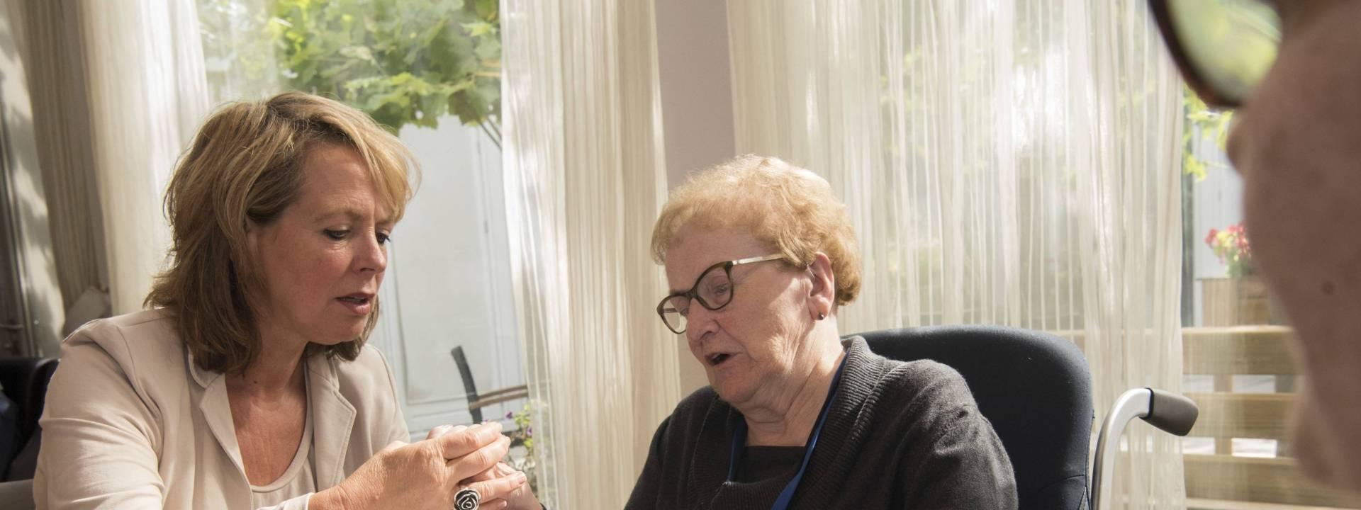 Vrijwilliger/mantelzorger samen met cliënt aan tafel bij La Famille